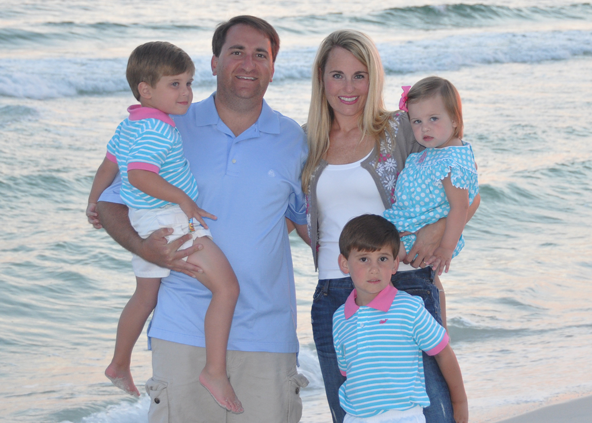 Justin Baird with wife and kids near the ocean